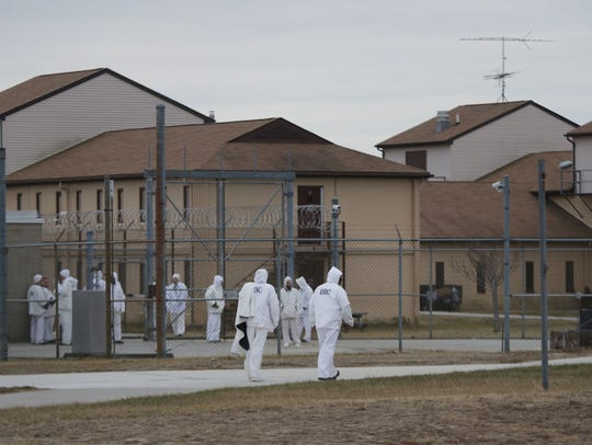 Inmates walk between buildings at James T. Vaughn Correctional