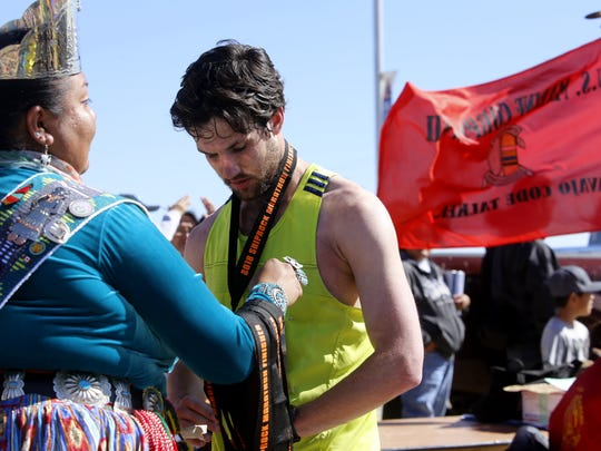 Daniel Ray receives a medal Saturday after finishing the Shiprock Marathon. Ray was the second runner to cross the finish line.