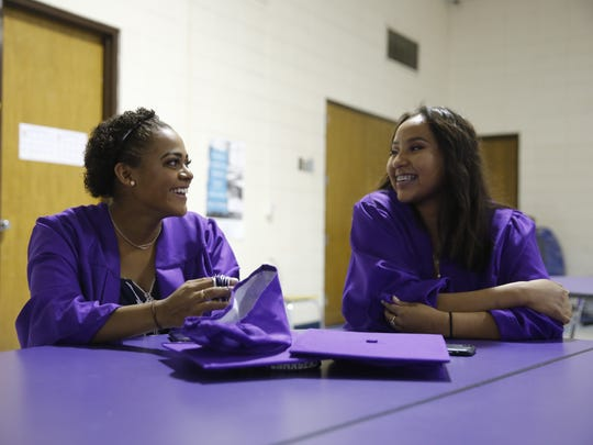 Kirtland Central High School seniors Aislinn Arthur, left, and Haleigh Begay talk to each other while waiting for their school graduation ceremony to start Friday in Kirtland.