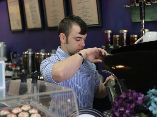 "Kade Buquoi, head barista at ""As the Crow Flies Coffee & Tea"" in Pineville, prepares a coffee drink."