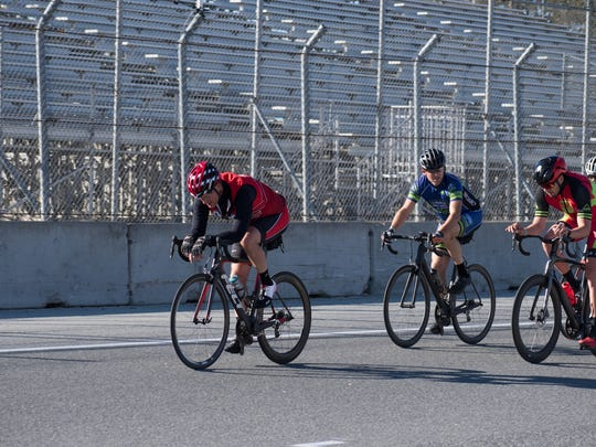 A group of riders sprint to the finish of a lap around Laguna Seca. Twilight rides around the track sometimes draw close to 100 riders in the summer around track events.