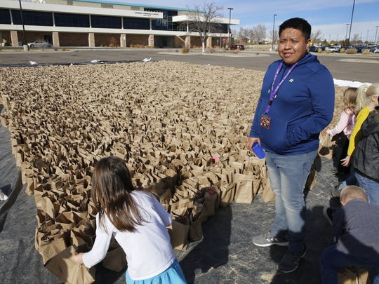 Work-study student Faron Lewis helps organize the efforts of Country Club Elementary School students Wednesday afternoon as they help put together luminarias for the college's annual display this weekend.