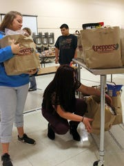 Deming Cesar Chavez Charter High School students load bags of donated food on to a cart to transport across the school for their classmates in need.  DCCCHS began work on an in-house food bank to provide additional meals for some of their students and families who are in need of assistance.