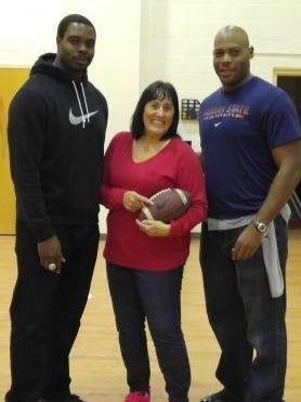 (From left) Dwayne Hendricks, a retired NFL player; Mary Lyons, a science teacher at Creative Achievement Academy; and Clifton Smith, a retired NFL player, used football to demonstrate laws of physics.