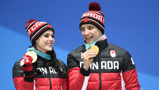 Tessa Virtue and Scott Moir (CAN) celebrate winning the gold medal in the figure skating free dance event.