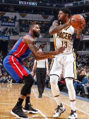 Pacers forward Paul George is guarded by Pistons forward Marcus Morris.