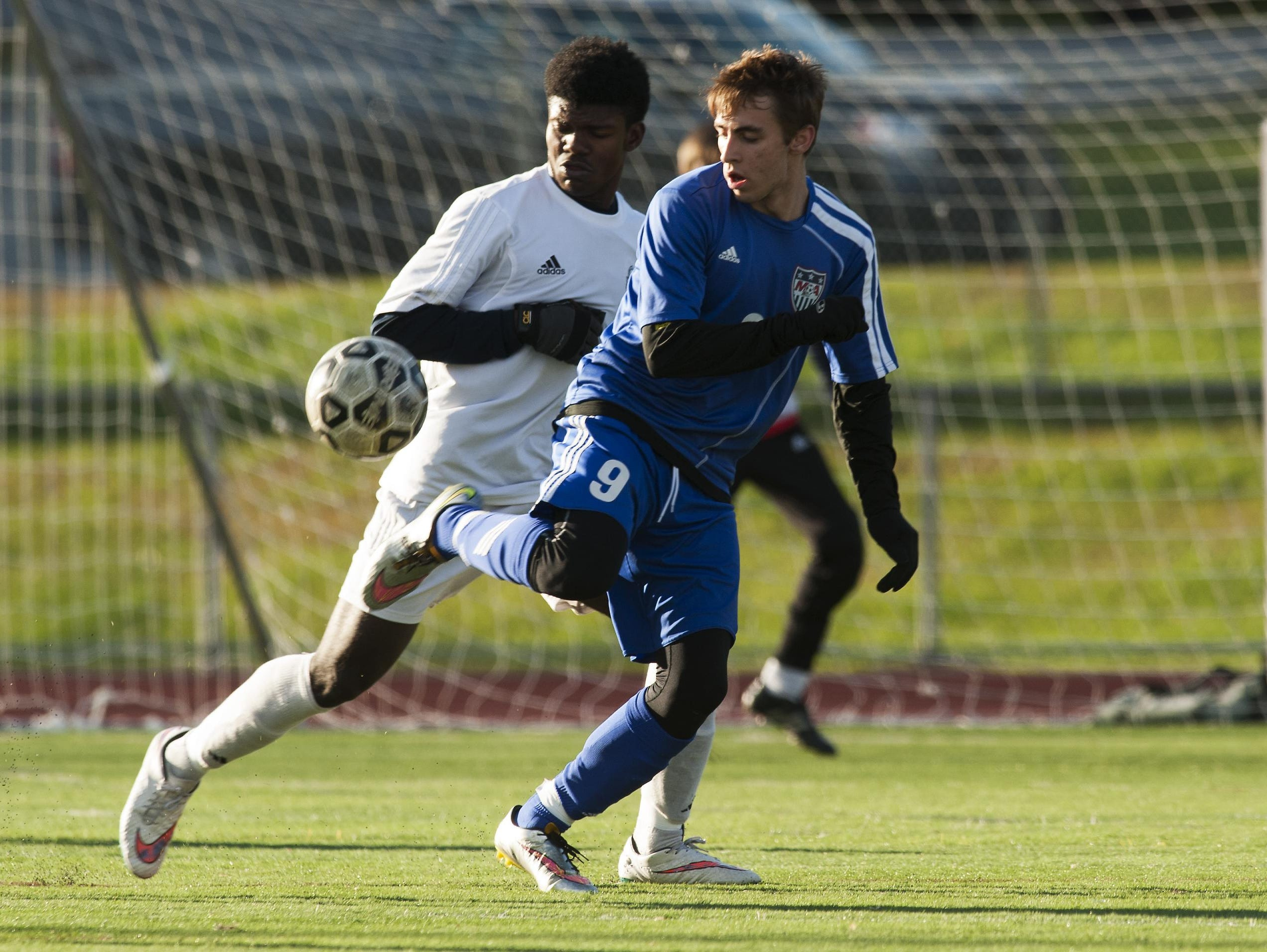 Mount Anthony's Carter Bentley (9) plays the ball in front of Burlington's Maenda Bienfait Badibang (21) during a Division I high school boys soccer quarterfinal at Buck Hard Field on Friday.
