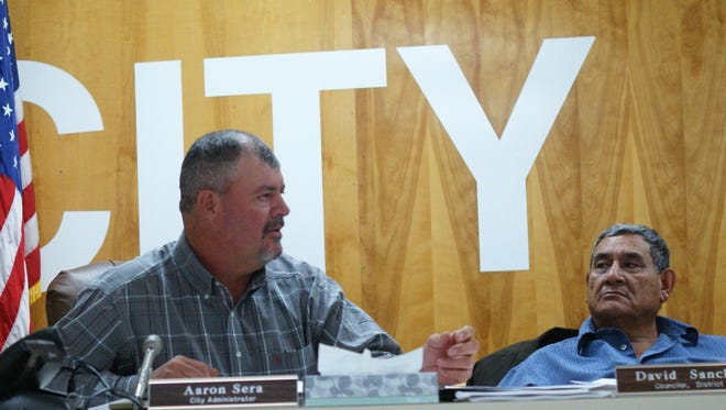 Deming City Councilor David Sanchez, right, listens as Administrator Aaron Sera, left, talks about elected officials' salaries.