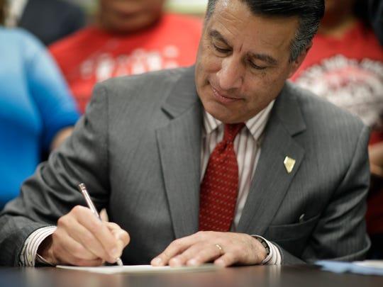 Gov. Brian Sandoval signs a bill June 15 in North Las Vegas.