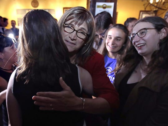 Vermont Democratic gubernatorial candidate Christine Hallquist, center, a transgender woman and former electric company executive, embraces supporters after claiming victory during her election night party in Burlington, Vt., Aug. 14, 2018.