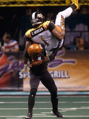 Allen Chapman tackles LA KISS' Donovan Morgan after Morgan jumped for the catch during the fourth quarter of an arena football game at US Airways Center in Phoenix on June 21, 2014.
