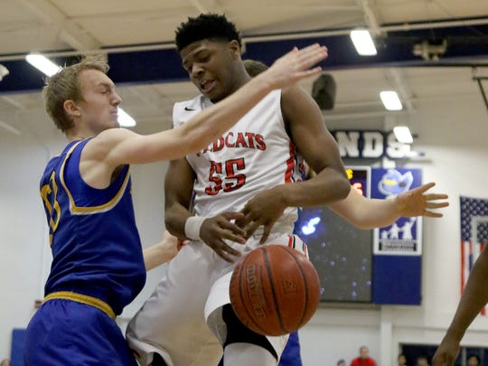 Newport's MeKell Burries (55) has the ball knocked away by Newport Central Catholic's Paul Kremer during their district game, Friday, Feb.23,2018.