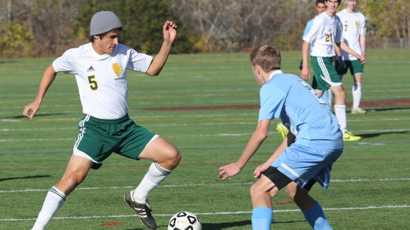 Hastings' John Ceballos moves the ball in front of Rye Neck's Tim Kelly at the Section One Class B boys final at Arlington High School, Oct. 31, 2015.