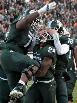 Gerald Holmes is mobbed by teammates Connor Cook (18) and Tyler Higby (70) Saturday.