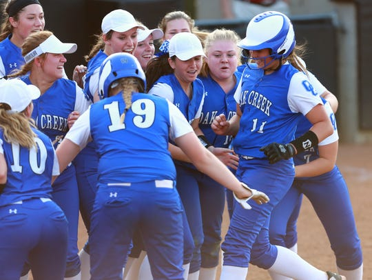 Oak Creek pitcher Becca Oleniczak (#11) gets a warm welcome at home plate after hitting a solo home run.