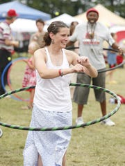 Kelly Ritter, of Freeville, tries her skill at the hula hoop Friday at the GrassRoots festival in Trumansburg. In the background, with a hula hoop, is Paul Thomas, of Ithaca.