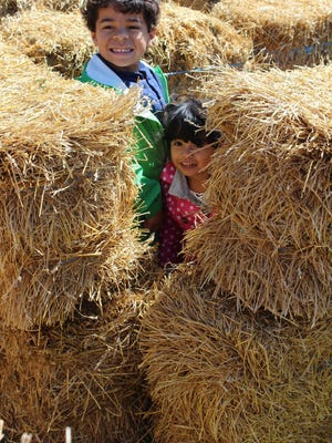 Parker and Maybelle Burke from Mendon peek out from the straw maze at Lollypop Farms' Heroes for Horses Day on Sunday