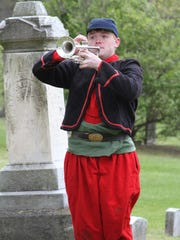 Brandon Sexton, a member of the Hartland High School History Club, plays Taps Sunday at the dedication of American Revolution patriot Willard Church's grave in Hodge Cemetery.