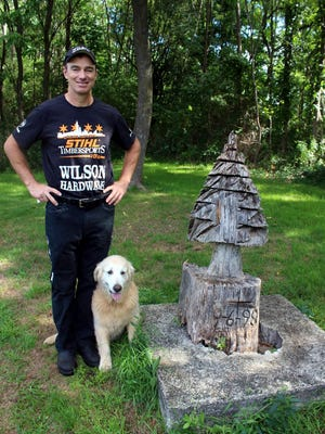 Dave Jewett is pictured with his dog, Tommy, near a little Christmas tree he carved almost 20 years ago along the Erie Canal Heritage Trail.