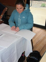 Lindsay Ball, a student at The College at Brockport, reads a menu in Braille at Grinds 122 Café in Brockport.