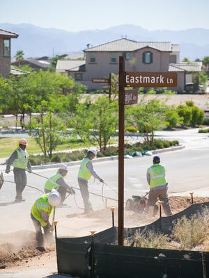 Crews work on a sidewalk in the high-end residential area of the Eastmark mixed-use community in Mesa. Plans between the developer and city are coming to fruition.