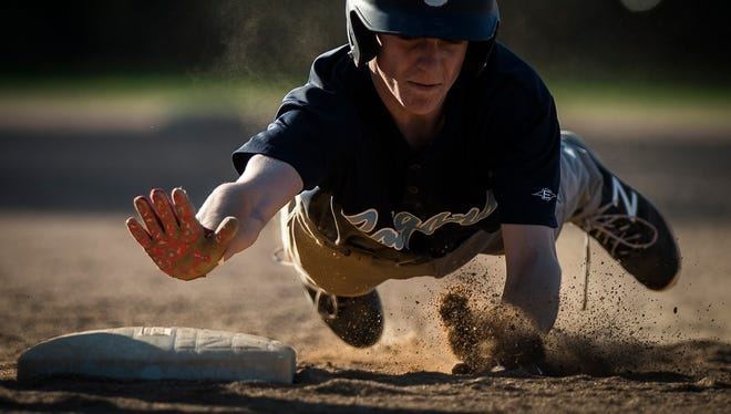 MMU's #1 Cooper Knight dives for first base to beat the pick off during their baseball game Wednesday night, May 9, 2018, in Colchester. MMU won, 8-4.