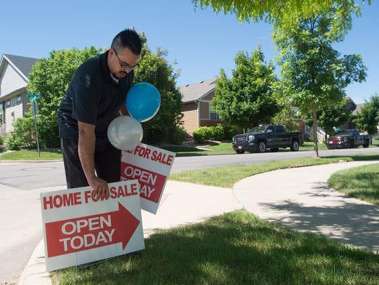 Realtor Chance Basurto sets up signs to showcase a