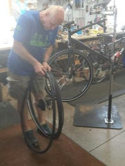 Sports Den owner Dennis Riedel fixes a bike tire in
