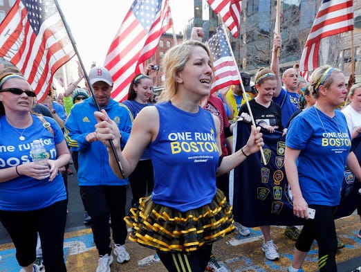 Participants in a cross country charity relay that began in March in California cross the finish line of the Boston Marathon in Boston, Sunday, April 13, 2014. Boston Marathon bombing survivors, family members and supporters joined the relay runners for the final half-block to the finish.