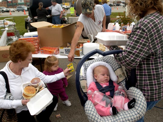 SUNG H. JUN / Courier & Press Regina Boarman, left, helps her grand daughter, Mia Jaranowski, 2, take a snack from a volunteer as Mia's mother, Natalie, right, and 3 months old sister Miranda waits for it at the parking lot of CVS on Lloyd Expressway and I-261 in Newburgh Monday afternoon. CVS and Logan Roadhouse served free lunch and drink for tornado victims and workers.