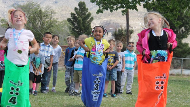 Josephin Schubert, Sa'dora Coles and Olivia McNees, kindergarteners at Yucca Elementary, complete the sack race portion of the obstacle course celebrating their achievements in math.