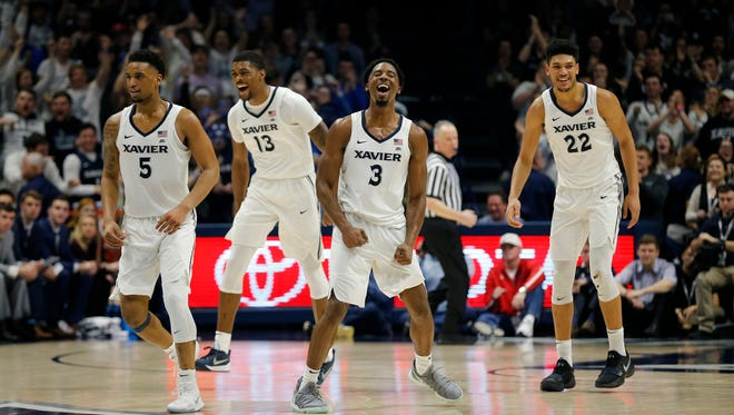 Xavier Musketeers guard Quentin Goodin (3) and the Musketeers back court celebrate after Trevon Bluiett's dunk in the second half of the NCAA Big East game between the Xavier Musketeers and the Providence Friars at the Cintas Center in Cincinnati on Wednesday, Feb. 28, 2018. The Musketeers won their first-ever Big East regular season title with an 84-74 win over Providence.