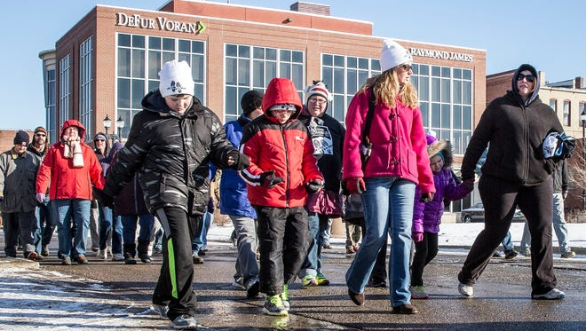 Hundreds walk down South Walnut St. Saturday morning for the Muncie Mission's Walk a Mile in My Shoes fundraiser. This year's fundraising goal was $90,000.