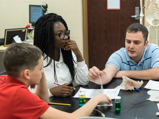 Cayden Gibson (left to right) and Ashlee Givens receive help from their eighth-grade science teacher George Ennulat III as they work on a hands-on enrichment activity at Lodge Community School. The students measured the density of fluids by layering colored salt solutions together to see which colors sank or stayed at the top.