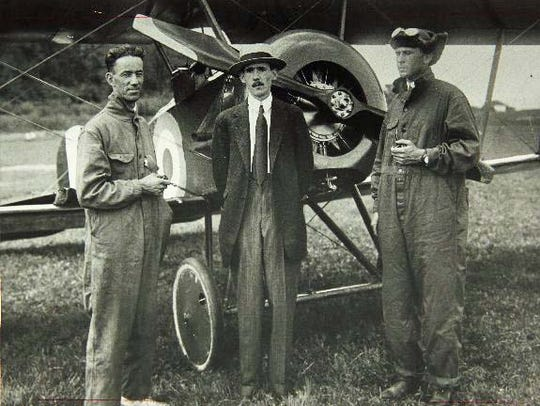 Designer B.D. Thomas stands at the center of the photo
