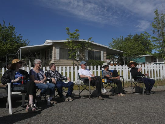 Neighbors watch as a mobile home is demolished in their