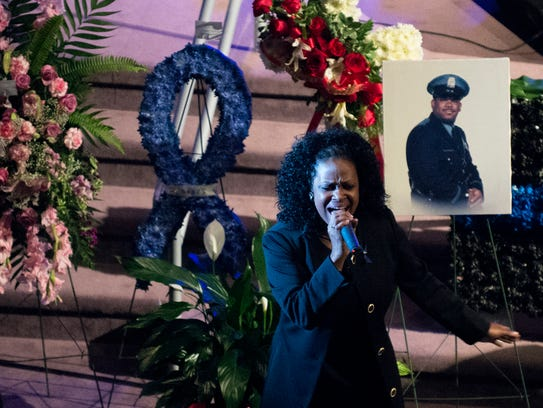 Priscilla McCoy speaks to gatherers as a memorial service