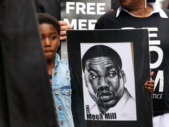 Rapper Meek Mill's son Papi holds a sign as protesters