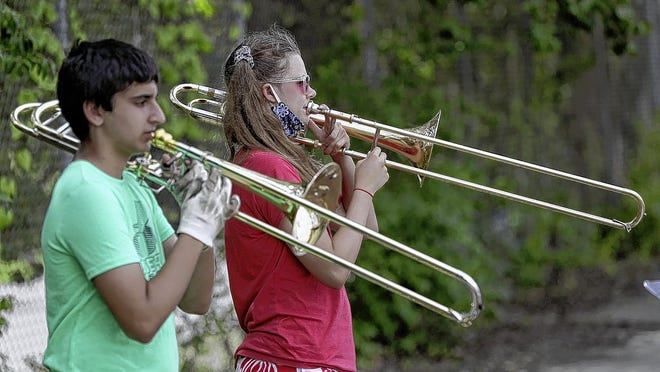 Bishop Watterson High School students Nick Marszal, 17, and Lucia Cherok, 16, rehearse during band practice Aug. 12 outside the school in Clintonville. The marching band is looking at 2020-21 as a year to learn, rather than focusing on performances, which may or may not be feasible, leaders say.