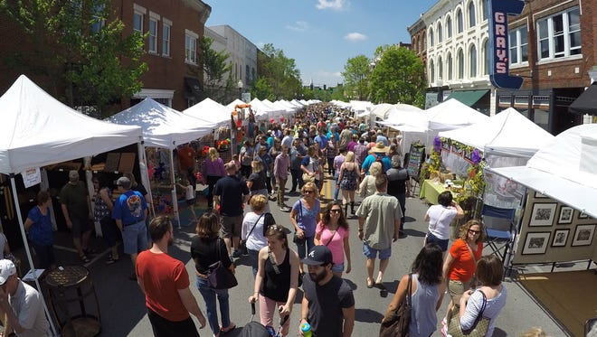 People walk down Main Street looking at the arts and crafts for sale at the 33rd Annual Main Street Festival in downtown Franklin on April 23, 2016.