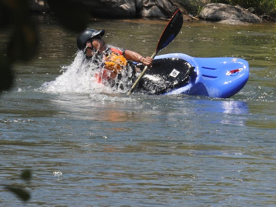 A man rolls his kayak in the Truckee River near Rock Park Monday July 14, 2014.
