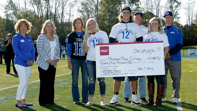 Mitch Kramer's family presented this $25,000 check to Thomas More College on senior day to establish a scholarship fund in his honor. His siblings Molly, Mason and Paige are holding the check, joined by parents Kathy and Jim Kramer.