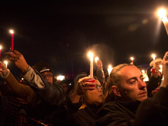 Community members raise their candles during vigil for Mitchual Sam and Hjordis Sam on Friday in Kirtland.