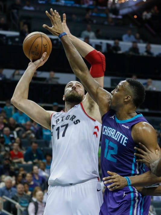 Toronto Raptors center Jonas Valanciunas, of Lithuania, shoots against Charlotte Hornets center Dwight Howard in the second half of an NBA basketball game in Charlotte, N.C., on Sunday, Feb. 11, 2018. Toronto won 123-103. (AP Photo/Nell Redmond)