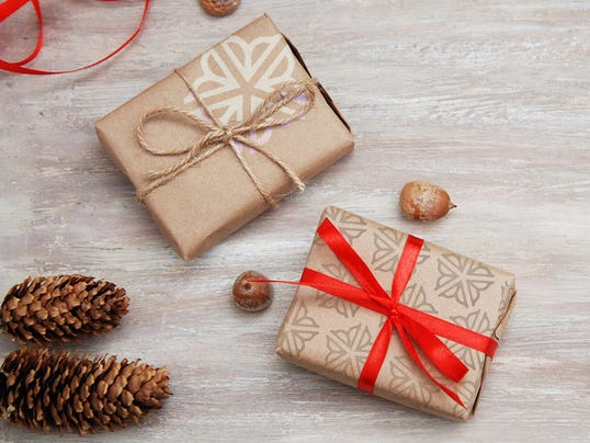 Present box from brown papaer with red ribbon bow on rustic background