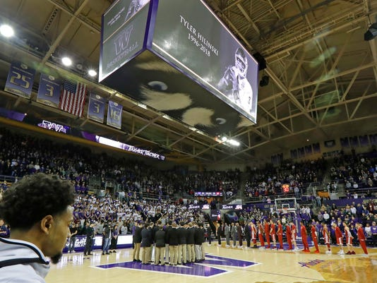 Washington and Washington State players and coaches join the crowd in a moment of silence, Sunday, Jan. 28, 2018, before an NCAA college basketball game in Seattle, in memory of Washington State football quarterback Tyler Hilinski, who police said committed suicide Jan. 16, 2018, in his apartment in Pullman, Wash. (AP Photo/Ted S. Warren)