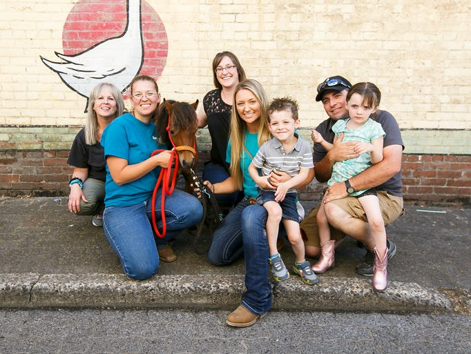 The Wetherford family pose for a photo with Horses