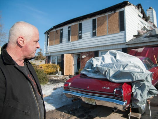 Joe Parisi looks at his family's Williamstown home that was destroyed by fire Sunday morning.   Parisi's daughter Donna, 25, is a volunteer firefighter with the Williamstown Fire Company.  The fire company launched a collection for the family Monday seeking monetary donations and gift cards for groceries and essentials.