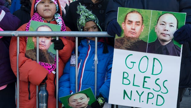 Mourners stand at a barricade near Christ Tabernacle Church, in the Glendale section of Queens, as the casket of New York Police Department officer Rafael Ramos arrives for his wake, Friday, Dec. 26, 2014, in New York.