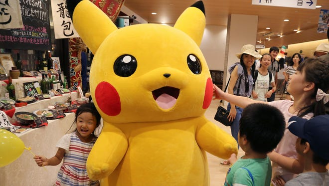 Pikachu is surrounded by children during a Pokemon festival in Tokyo, Monday, July 18, 2016.